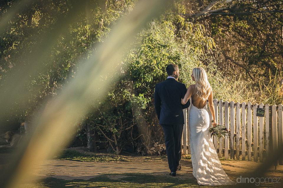 newlyweds walk around flora farms in charming wedding photo by d